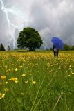 Woman into the field. Woman looking the lightning in the field Royalty Free Stock Photo