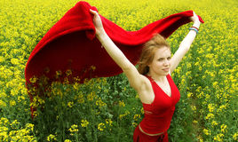 Woman in field. Young woman with red dress and flying cape in a field of yellow flowers stock photo