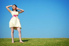 Woman in field. A beautiful young woman in a field with a blue sky. Copy space stock photography