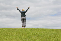 Woman in field with arms raised. Royalty Free Stock Photo