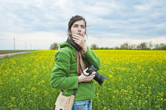 Woman in field with camera Stock Image