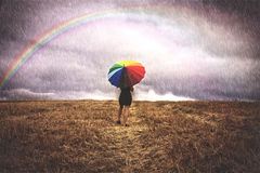Woman in field with colorful umbrella in the rain Royalty Free Stock Photography