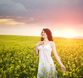 Woman in field with flowers at summer sunset. Royalty Free Stock Images