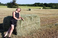 Woman leaning on a Hay Bale. Woman in a field leaning on a Hay Bale in the sunshine royalty free stock photo