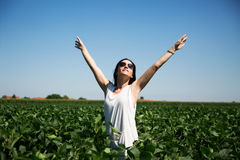 Woman in field smiling and spreading hands happy Stock Images