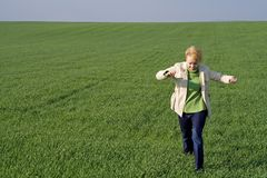 Woman on the field at spring. Woman hopping and running on a green wheat field in springtime stock photography