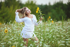 Woman in field with sunflower in hand. Stock Photos