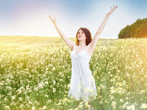 Woman in field with yellow flowers at summer sunset. Royalty Free Stock Photos