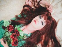 Woman with fiery red hair close up. Lying down. Woman with fiery red hair lies on pale damask background holding red roses, making eye contact. Creative filters royalty free stock photo