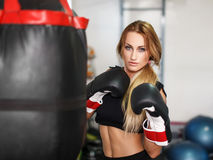 Woman fighter with heavy bag in gym. Woman fighter in gloves with heavy bag in gym Royalty Free Stock Image