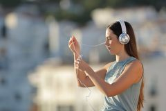 Woman fighting with the headphones cord. Frustrated woman fighting with the headphones cord in the street royalty free stock images