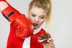 Woman boxing chocolate cupcake. Woman fighting with her bad habits, being on diet. Female wearing boxing glove holding sweet dessert, chocolate cupcake royalty free stock images