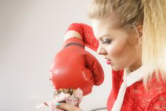 Woman fighting off bad food, boxing chocolate cake Royalty Free Stock Photo