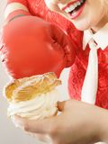 Woman fighting off bad food, boxing cream puff cake Stock Photo