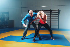 Woman fights with man, self defense technique. Self-defense workout with personal trainer in gym, martial art royalty free stock photos