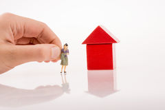 Woman figure nearby a house made of blocks Royalty Free Stock Photography