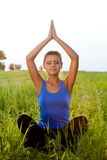 Woman on filed in lotus pose Royalty Free Stock Photography