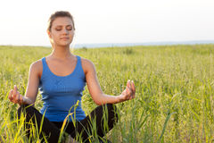 Woman on filed in lotus pose Stock Photography