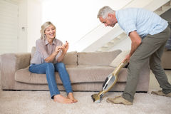 Woman filing nails while man vacuuming area rug Stock Photo