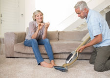 Woman filing nails while man vacuuming area rug Stock Photography