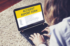 Woman fill in an accident report form in a laptop. Royalty Free Stock Image