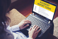 Woman fill in an accident report form with a laptop by internet. Stock Photography