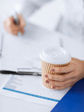 Woman filling in form and drinking coffee Royalty Free Stock Photos