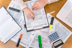 Woman filling 1040 individual tax form. Office work royalty free stock photo