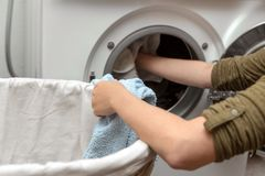 Woman filling laundry in the washing machine, housewife and hygienic. Close up, woman filling laundry in the washing machine, housewife and hygienic royalty free stock photos