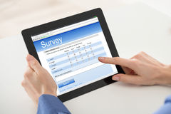 Woman Filling Online Survey Form On Digital Tablet Royalty Free Stock Photos