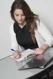 Woman filling out form. While sitting at table royalty free stock images