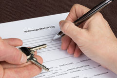 A woman is filling out a german tenancy agreement with keys in h stock photos