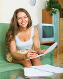 Woman filling papers at home Stock Photo