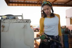 Woman filling petrol in car at petrol pump. On a sunny day Stock Image
