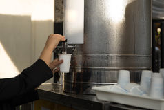 Woman filling plastic cup at water cooler Royalty Free Stock Photography
