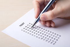 Woman filling test sheet with answers Stock Image