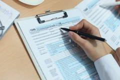 Woman filling in U.S. Individual income tax return, tax 1040 at table. Woman filling in U.S. Individual income tax return, tax 1040 at table royalty free stock photo