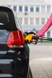 Woman filling up car at petrol station. Black car Royalty Free Stock Photography
