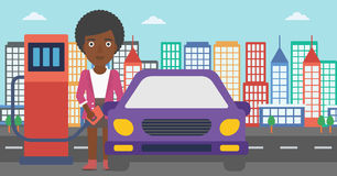 Woman filling up fuel into car. An african-american woman filling up fuel into the car on a city background vector flat design illustration. Horizontal layout Stock Image