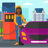 Woman filling up fuel into car. An african-american woman filling up fuel into the car on a city background vector flat design illustration. Square layout Royalty Free Stock Photo