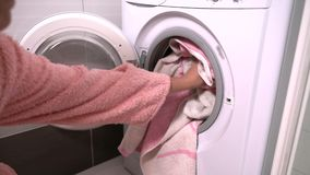 Woman filling a washing machine with laundry. Woman filling a washing machine with dirty laundry then closing the door to commence the wash stock footage