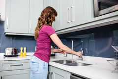 Woman filling water in glass at kitchen counter Royalty Free Stock Photos
