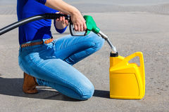 Woman filling yellow can with gasoline or petrol royalty free stock photo