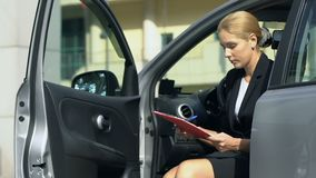 Woman fills car rent insurance form, sitting in automobile, business trip. Stock footage stock footage