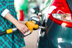 Woman fills petrol into the car at a gas station Stock Image