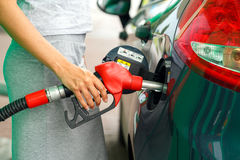 Woman fills petrol into the car at a gas station Royalty Free Stock Photos