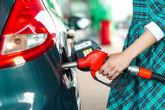 Woman fills petrol into the car at a gas station Royalty Free Stock Image