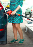 Woman fills petrol into the car at a gas station Stock Images