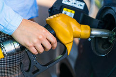Woman fills petrol into the car at a gas station Stock Photography