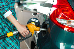Woman fills petrol into her car at a gas station Royalty Free Stock Images
